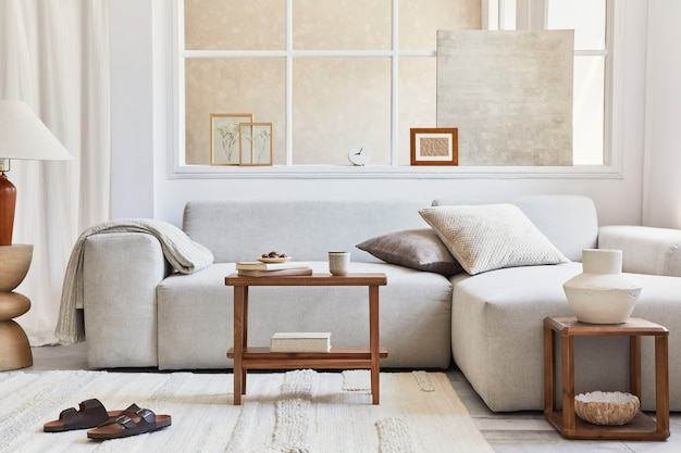 Kreatywna kompozycja stylowego i przytulnego wnętrza salonu z makietą, szarą narożną sofą, oknem, stolikami kawowymi i osobistymi akcesoriami. beżowe, neutralne kolory. szablon.