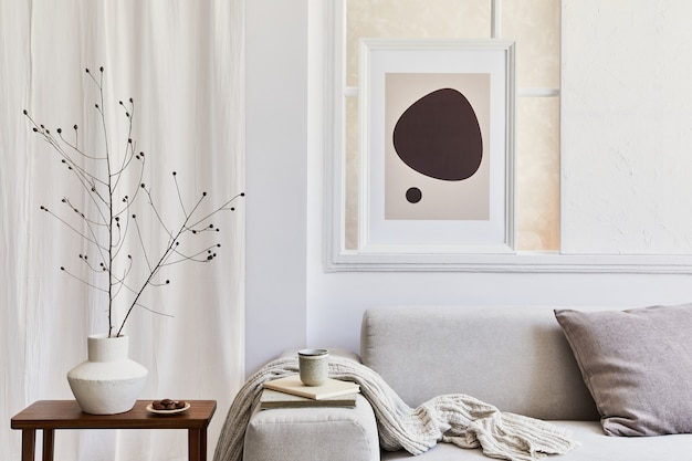 Kreatywna kompozycja stylowego i przytulnego wnętrza salonu z mocną ramą plakatową, szarą narożną sofą, oknem, stolikiem kawowym i osobistymi akcesoriami. beżowe, neutralne kolory. szablon.