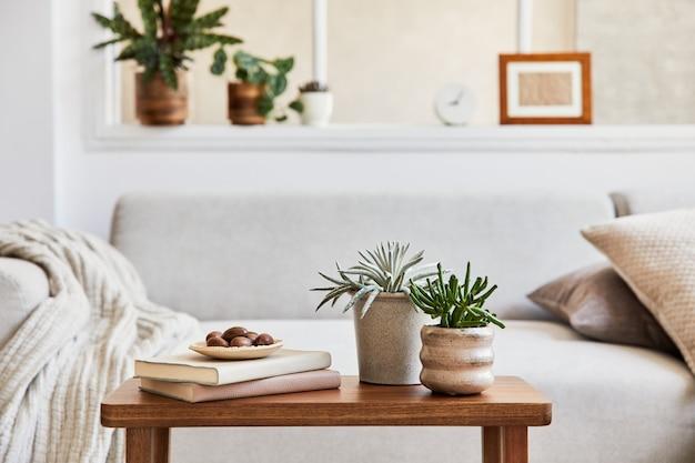 Kreatywna kompozycja stylowego i przytulnego wnętrza salonu z szarą narożną sofą, oknem, roślinami na stoliku kawowym i osobistymi akcesoriami. beżowe, neutralne kolory. detale. szablon.