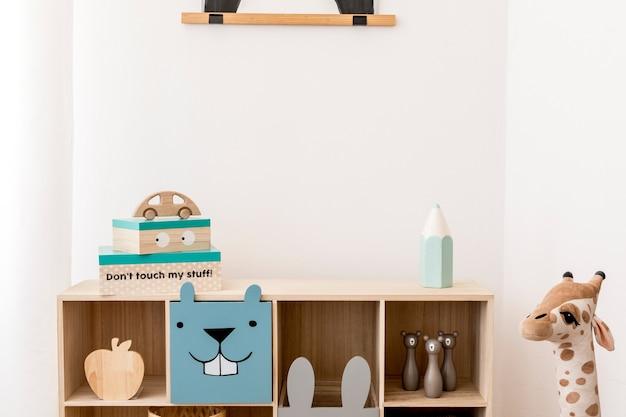 Kreatywna kompozycja stylowego i przytulnego wystroju pokoju dziecięcego z białą ścianą, pluszowymi zabawkami, komodą i akcesoriami. skopiuj miejsce. szablon.