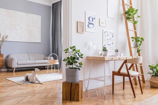 Kreatywna kompozycja stylowego skandynawskiego wystroju wnętrz biurowych z ramami plakatowymi, drewnianym biurkiem, krzesłem, roślinami i dodatkami. ściany neutralne, parkiet.