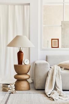 Kreatywna kompozycja stylowego wnętrza salonu z mocną ramą plakatową, szarą narożną sofą, oknem, zaprojektowanym stolikiem kawowym, lampą i osobistymi akcesoriami. beżowe, neutralne kolory. detale. szablon.