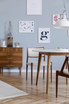Kreatywna kompozycja stylowego wystroju wnętrza salonu scandi z mocnymi ramami plakatowymi, drewnianą komodą, krzesłem, roślinami i dodatkami. ściany neutralne, parkiet. szablon.