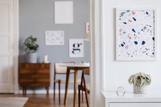 Kreatywna kompozycja stylowego wystroju wnętrza salonu scandi z mocnymi ramami plakatowymi, sofą, drewnianą komodą, krzesłem, roślinami i dodatkami. ściany neutralne, parkiet. szablon.