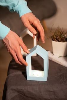 Kreatywna kompozycja stylu życia. minimalistyczny świecznik betonowy w kształcie domu w kolorze niebieskim z palącą się woskiem sojowym świeca zapachowa w męskich rękach. naturalne materiały. doniczka z suszonymi kwiatami