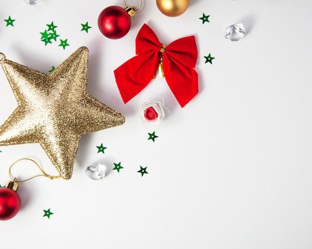 Kreatywna kompozycja świąteczna wykonana z bombek i ozdób choinkowych z czerwoną wstążką na białej ramce dekoracyjnej płasko świeci widok z góry