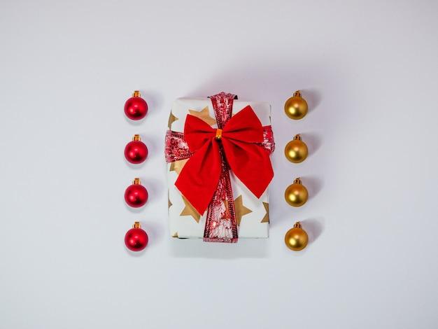 Kreatywna kompozycja świąteczna wykonana z pudełka z czerwoną wstążką i bombkami świątecznych dekoracji złota i czerwieni płasko świeci widok z góry