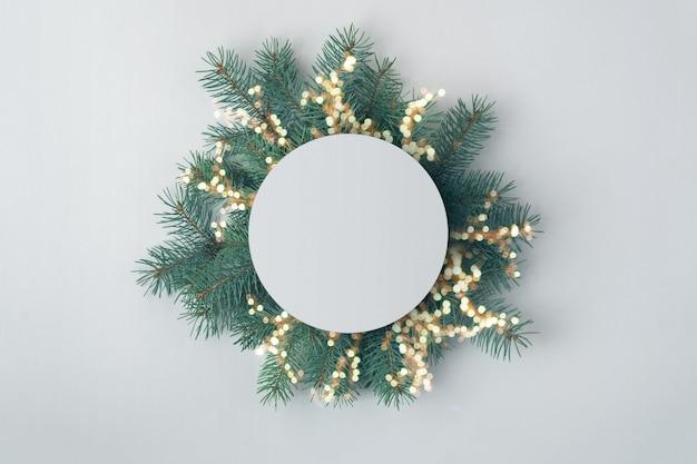 Kreatywna kompozycja świąteczna z gałęzi świerkowych i okrągła pusta karta. układ świąteczny.