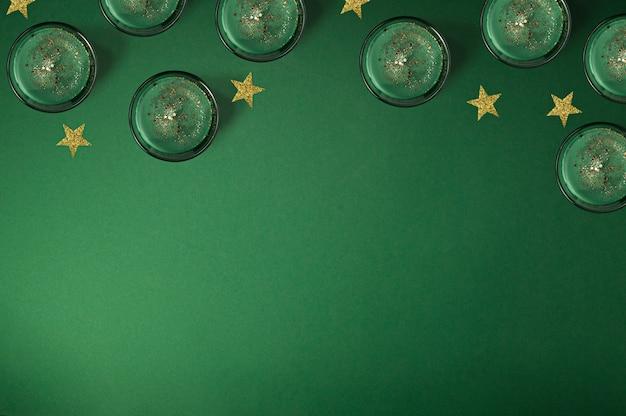Kreatywna kompozycja świec zapachowych i błyszczących złotych gwiazd na zielonym tle, świąteczna ramka z miejscem na kopię, płaski układ, widok z góry
