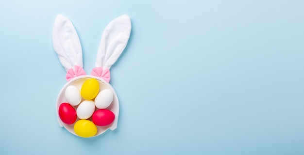 Kreatywna kompozycja wielkanocna. wielkanocni jajka i królików ucho na błękitnym tle. skopiuj miejsce