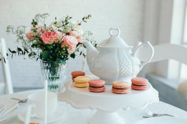 Kreatywna kompozycja wiosenna. eleganckie słodkie macarons deserowe, filiżanka herbaty lub kawy i piękny pastelowy bukiet beżu i żywych koralowych kwiatów