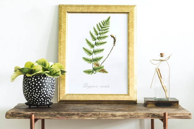 Kreatywna kompozycja wystroju domu z ramą plakatową, drewnianą konsolą, roślinami w zaprojektowanych przez hipsterów doniczkach i dodatkami