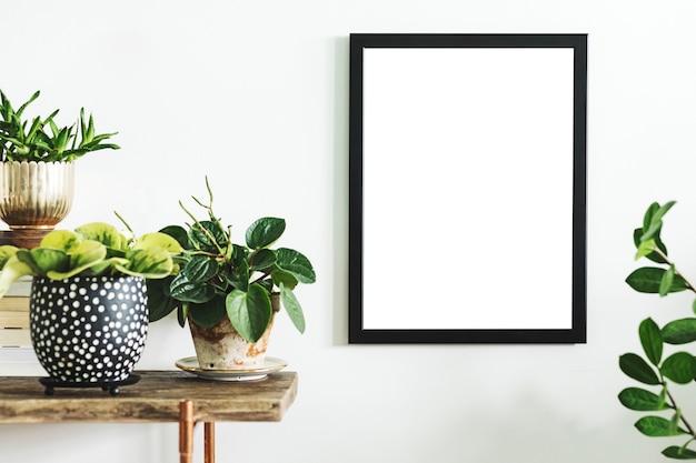 Kreatywna kompozycja wystroju wnętrza domu z mocną ramą plakatową, drewnianą konsolą, roślinami w hipsterskich donicach i akcesoriami. natura i rośliny kochają koncepcje.