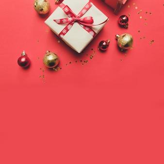 Kreatywna kompozycja z czerwonym pudełkiem, wstążkami, dużymi i małymi kulkami z czerwonego złota, świątecznymi dekoracjami na czerwono.