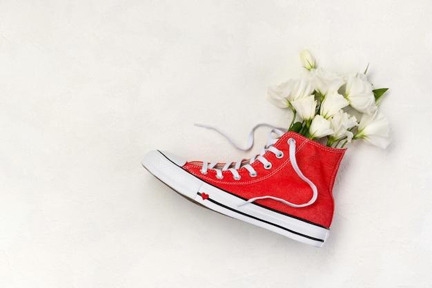 Kreatywna kompozycja z czerwonymi trampkami i kwiatami na białym tle. urodziny dzień matki dzień matki kartkę z życzeniami.