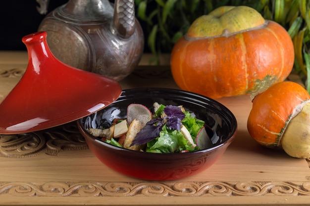 Kreatywna kompozycja z dynią, orientalnym dzbankiem i gotową świeżą sałatką w studio. jesienna kompozycja