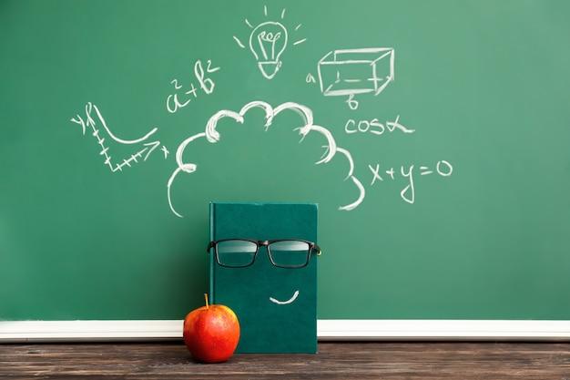 Kreatywna kompozycja z notatnikiem, jabłkiem i tablicą szkolną