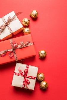 Kreatywna kompozycja z prezentów lub prezentów, złote kokardki czerwone tło.