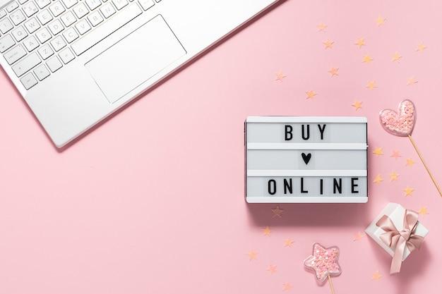 Kreatywna kompozycja z tekstem kup online na błyszczących dekoracjach lightbox i kolanach na różowym pastelowym tle