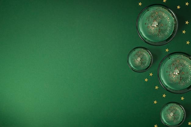 Kreatywna kompozycja ze świec zapachowych i lśniących złotych gwiazd na zielonym tle, świąteczna ramka z miejscem na kopię, układ płaski, widok z góry