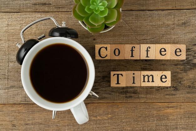 Kreatywna koncepcja filiżanka kawy i czas na kawę tekstową na drewnianym tle