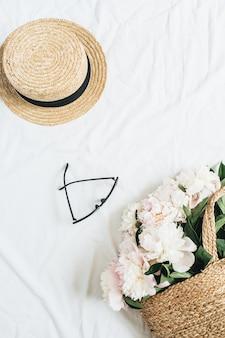 Kreatywna koncepcja kobieca z bukietem białych kwiatów piwonii w słomkowej torbie, okularach i słomkowym kapeluszu na białej powierzchni