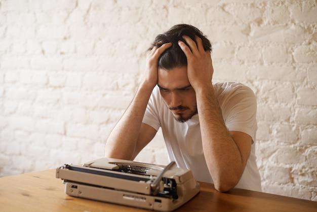 Kreatywna koncepcja kryzysu. brodaty hipster ma problemy z pisaniem wierszy.