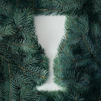 Kreatywna koncepcja na nowy rok. sylwetka kieliszek do szampana boże narodzenie z gałęzi choinki.