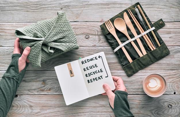 """Kreatywna koncepcja płaskiego, zerowego marnotrawstwa na lunch z drewnianymi sztućcami wielokrotnego użytku, pudełkiem na lunch w bawełnianej szmatce i filiżanką kawy wielokrotnego użytku. zrównoważony styl życia, tekst """"zmniejsz, użyj ponownie, poddaj recyklingowi, powtórz""""."""