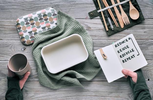 """Kreatywna koncepcja płaskiego, zerowego marnotrawstwa na lunch z drewnianymi sztućcami wielokrotnego użytku, pudełkiem na lunch w bawełnianej szmatce i filiżanką kawy wielokrotnego użytku. zrównoważony styl życia, tekst """"zmniejsz, wykorzystaj ponownie, poddaj recyklingowi, powtórz"""" w książce"""