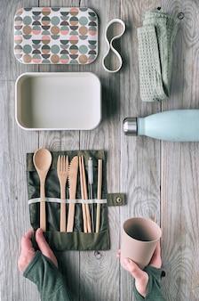 Kreatywna koncepcja płaskiego, zerowego marnotrawstwa na lunch z zestawem drewnianych sztućców wielokrotnego użytku, pudełka na lunch, butelki do picia i filiżanki do kawy wielokrotnego użytku. widok z góry na zrównoważony styl życia, płaski układ na postarzanym drewnie.