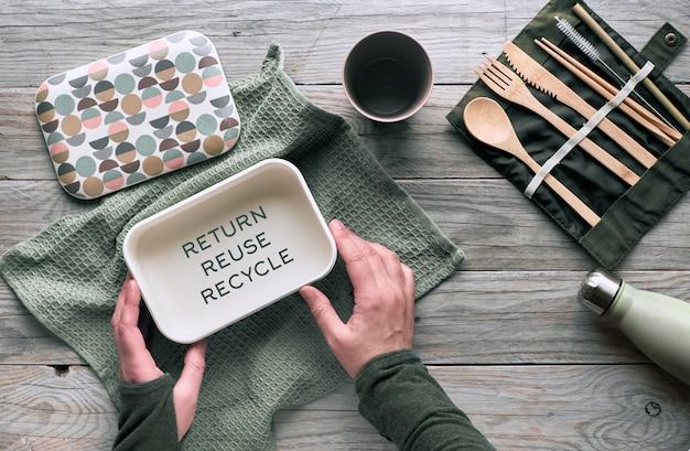 Kreatywna koncepcja płaskiego, zerowego marnotrawstwa na lunch z zestawem drewnianych sztućców wielokrotnego użytku, pudełka na lunch, butelki do picia i filiżanki do kawy wielokrotnego użytku.