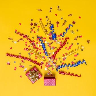 Kreatywna koncepcja z świątecznym wystrojem na żółtym tle. serca i gwiazdki konfetti, czerwone, żółte i niebieskie wstążki wylatują z czerwonego pudełka. wybuch konfetti.