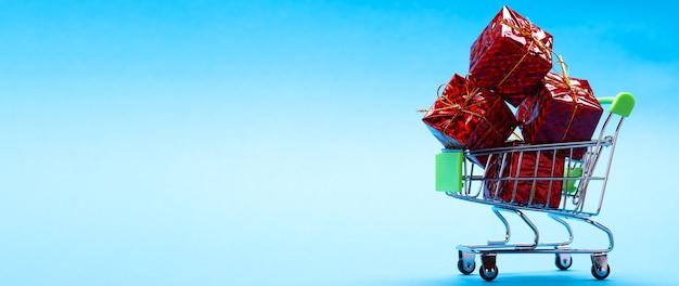 Kreatywna koncepcja z wózkiem na zakupy z prezentami na niebieskim tle z miejscem na tekst.