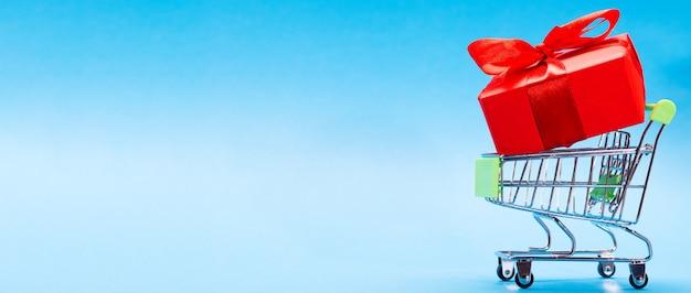 Kreatywna koncepcja z wózkiem na zakupy z prezentem na niebieskim tle z miejscem na tekst