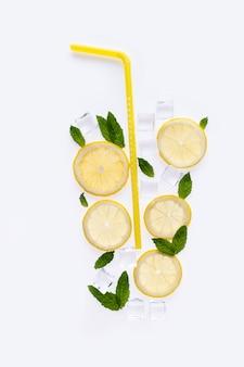Kreatywna letnia kompozycja napoju. z plasterkami cytryny, liśćmi mięty i kostkami lodu na białym tle