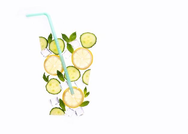 Kreatywna letnia kompozycja napoju. z plasterkami cytryny, liśćmi mięty, ogórkiem i kostkami lodu na białym tle