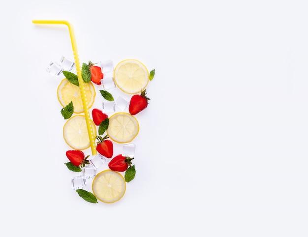 Kreatywna letnia kompozycja napoju. z plasterkami cytryny, liśćmi mięty, truskawkami i kostkami lodu na białym tle