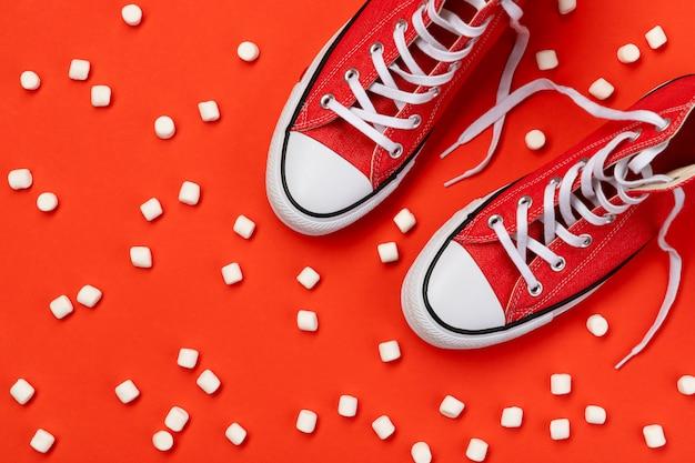 Kreatywna minimalna kompozycja z czerwonymi trampkami i pianką na czerwonym tle. szablon sprzedaży zakupów moda