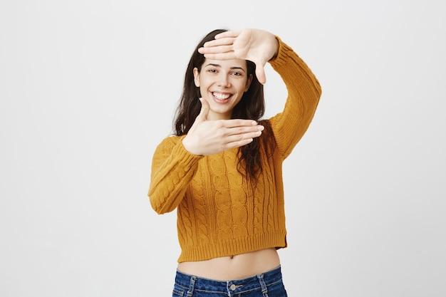 Kreatywna młoda dziewczyna szuka inspiracji, przeglądając ręczne ramki