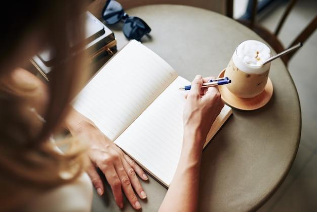 Kreatywna młoda kobieta pije kawę przy kawiarnianym stoliku i pisze w dzienniku swoje myśli i pomysły