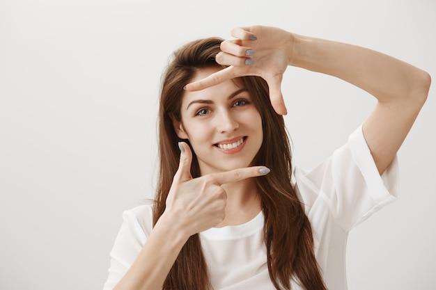 Kreatywna młoda kobieta robi gest przechwytywania, wyobrażając sobie scenę i uśmiecha się zadowolony