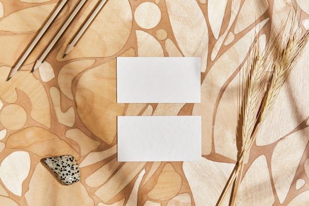 Kreatywna, płaska kompozycja wnętrz z makietami wizytówek, kamieniami, naturalnymi materiałami, ołówkami, suchymi roślinami i osobistymi akcesoriami. neutralne kolory, widok z góry, szablon.