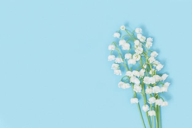 Kreatywna płaska kompozycja z wiosennych kwiatów białych konwalii na pastelowym niebieskim tle