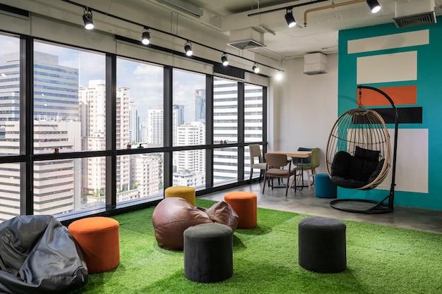 Kreatywna przestrzeń coworkingowa z poduszkami i krzesłami na sztucznej trawie w nowoczesnym biurze
