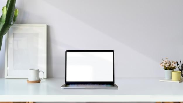 Kreatywna przestrzeń robocza. makieta plakat i pusty ekran laptopa na białym biurku