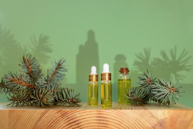 Kreatywna świąteczna kompozycja aromaterapii i spa z modnymi cieniami. niezbędny olej iglasty świerkowy w małych szklanych butelkach i zielonych gałązkach na drewnianym bukszpanu stoją na jasnozielonym tle.