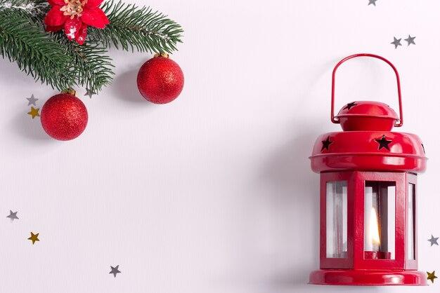 Kreatywna świąteczna ramka ze staromodną latarnią i gałązkami jodły ozdobiona błyszczącymi czerwonymi kulkami na szaro