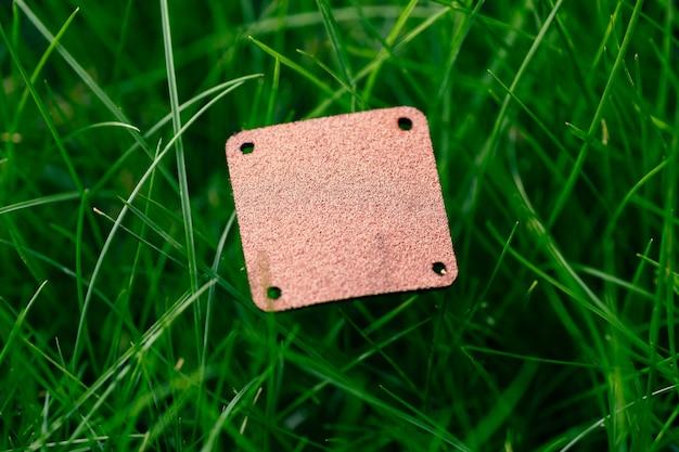 Kreatywna, układana rama do kompozycji wykonana z zielonego trawnika z kwadratową brązową skórzaną łatą na odzież na fabryczną płaską przestrzeń do układania i kopiowania logo.