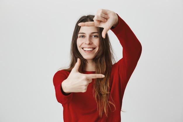 Kreatywna uśmiechnięta kobieta poszukująca inspiracji, wykonaj gest ramek aparatu